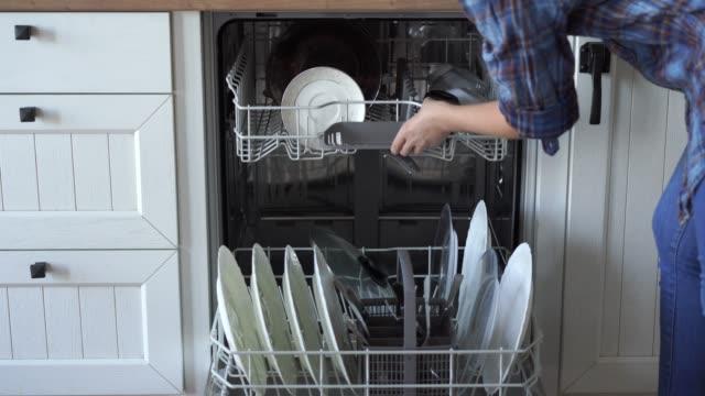 eine frau öffnet eine spülmaschine und nimmt sauberes geschirr - nutztier oder haustier stock-videos und b-roll-filmmaterial