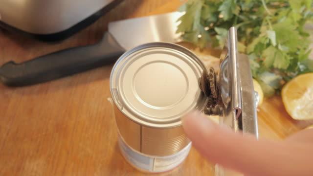 frau öffnet eine blechdose mit einem can opener - aluminium stock-videos und b-roll-filmmaterial
