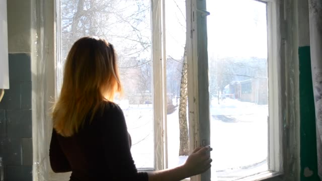 Woman opens a window at home in winter Woman opens a window at home in winter. Europeans Young girl opens a window into the street in winter frosty day. close to stock videos & royalty-free footage