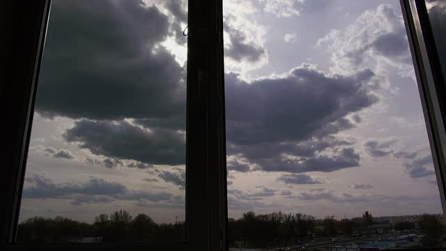 woman opens a window, beautiful clouds float across the sky video