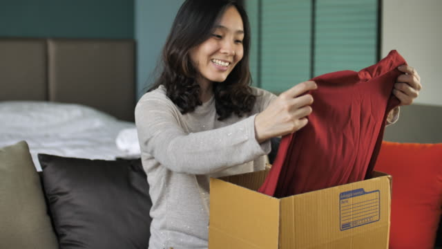 vídeos de stock e filmes b-roll de woman opens cardboard box while sitting on sofa - cardboard box