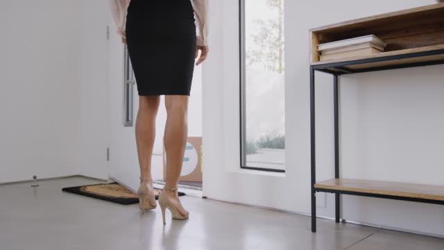 kvinnan öppnar dörren till huset och tar in courier leverans av mat från dörren - ytterdörr bildbanksvideor och videomaterial från bakom kulisserna