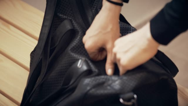 Woman opens gym bag Hands of a young woman opening bag in locker room, preparing for the workout,taking out sports clothing. positioning stock videos & royalty-free footage