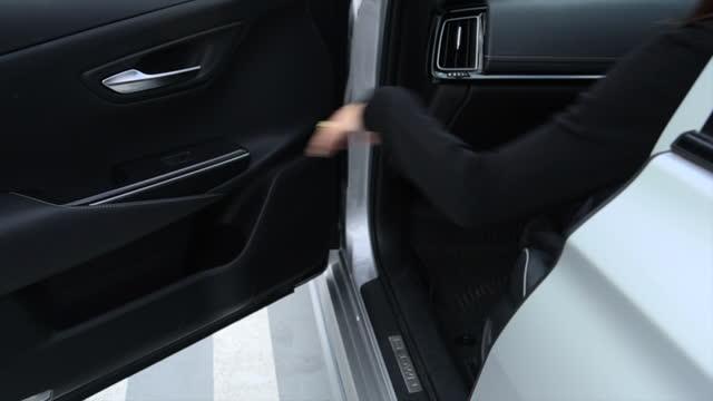 la donna apre la porta dell'auto e sale in macchina al parcheggio. donna che apre la porta dell'automobile. rallentatore. - sportello d'auto video stock e b–roll