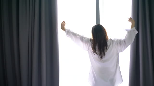 vídeos de stock e filmes b-roll de woman opens the curtains in the morning - acordar