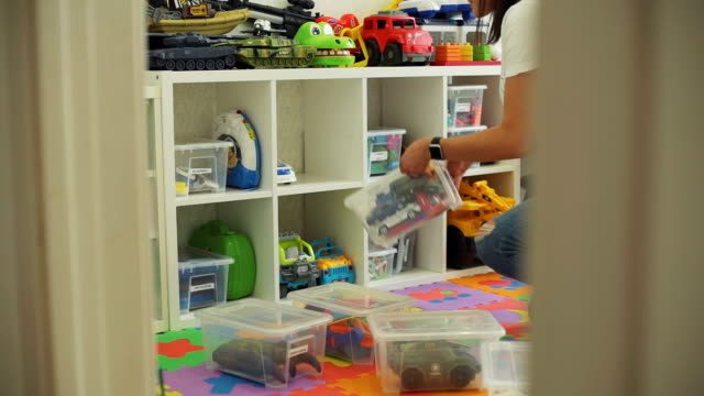 woman organizes toys and baby tries on clothes - giocattolo video stock e b–roll