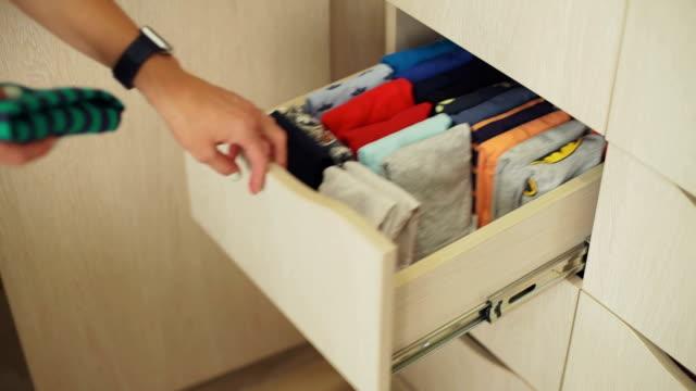 stockvideo's en b-roll-footage met vrouw het organiseren van kinderkleding in een kast - opruimen