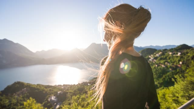 Woman overlooking mountain lake and lakeside village on a sunny summer day