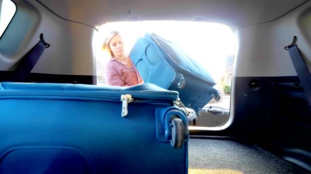stockvideo's en b-roll-footage met vrouw verpakking auto met bagage. - ingepakt