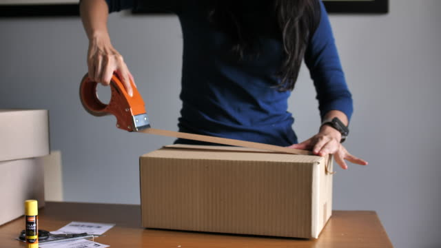 woman packing cardboard box with adhesive tape, moving out, migration, life change - inviare video stock e b–roll