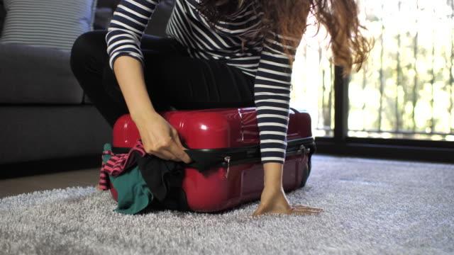 woman packing full suitcase - donna valigia solitudine video stock e b–roll