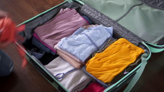女性は旅行のためのスーツケース パッキング - 荷造り点の映像素材/bロール