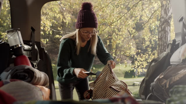 vídeos de stock e filmes b-roll de woman packing things in her backpack in the back of the car - mochila saco