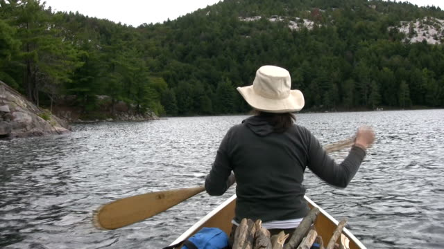 Woman paddles canoe. POV from stern. video
