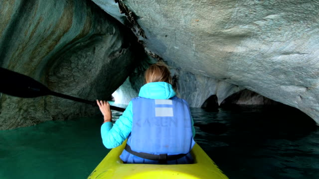 Woman paddles kayak Woman paddles kayak and explores caves named Marble Caves on the lake of General Carrera near the town of Puerto Rio Tranquilo in Patagonia, Chile cave stock videos & royalty-free footage