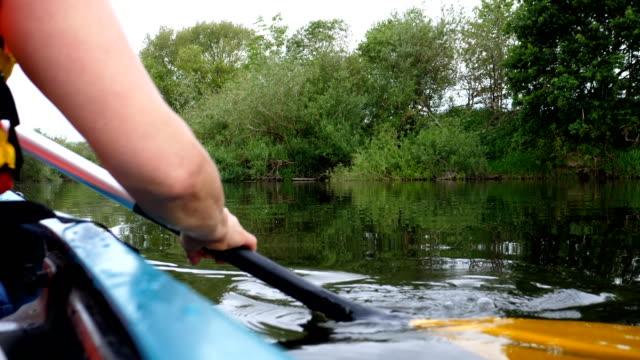 vidéos et rushes de vue latérale de kayak de pagayage de femme - kayak