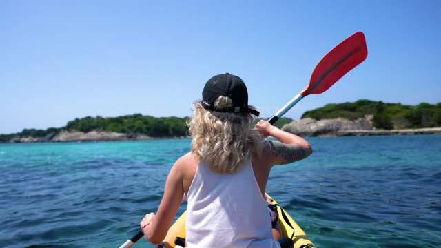 woman paddling on crystal clear water in boat next to shore in slow motion - d'atmosfera video stock e b–roll
