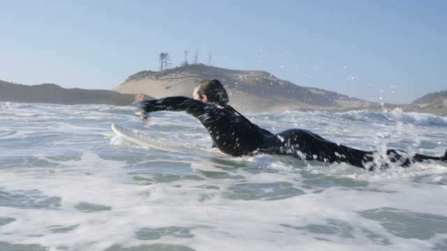 woman paddling out on her surfboard - 30 34 anni video stock e b–roll