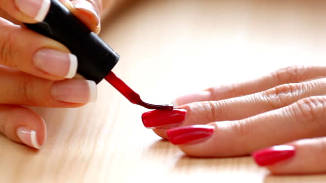 женщина painging ее fingernails. - ноготь на руке стоковые видео и кадры b-roll