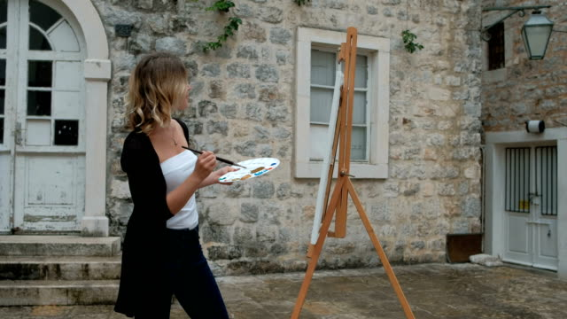 Woman painter paints picture on easel standing outdoors video