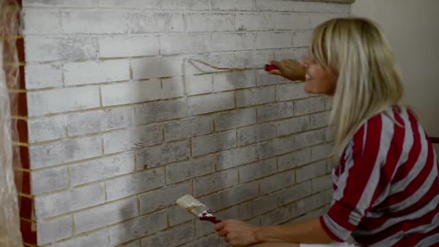 Mur de briques femme peinture avec rouleau à peinture. Idées de décoration de la maison. - Vidéo