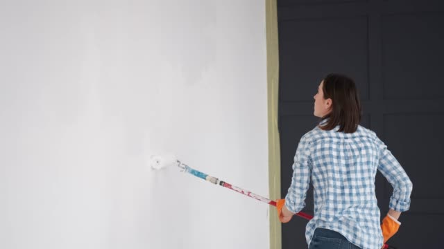 Woman painting wall with a roller at home video
