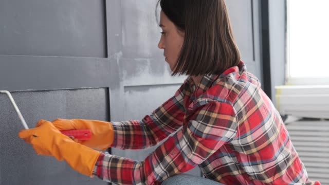 Woman painting wooden wall
