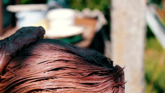 Woman paints her hair with brown paint in the summer on the street. Hair coloring at home A woman paints her hair with brown paint in the summer on the street. Hair coloring at home highlights hair stock videos & royalty-free footage