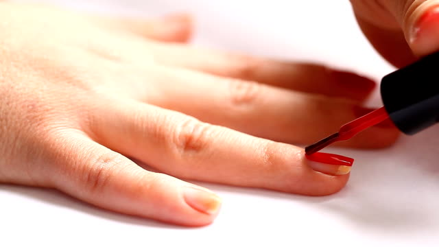 woman paints her nails with red lacquer video