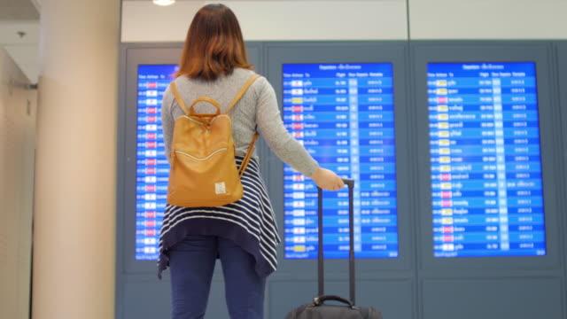 女性の乗客は出発ターミナル空港にてチェックイン前にデジタルの出発掲示板と携帯電話に彼女のフライトをチェック - 乗客点の映像素材/bロール