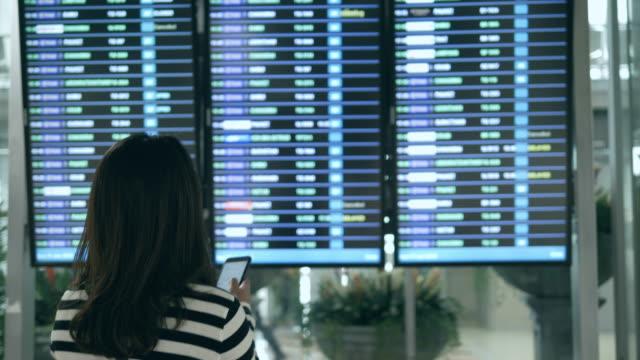 woman passenger checking her flight - табло вылетов и прилётов стоковые видео и кадры b-roll
