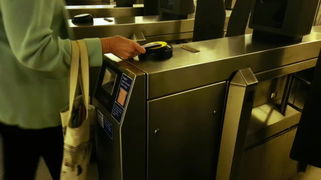 woman passing through fare gate in london underground station - contactless payment stock videos & royalty-free footage