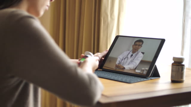 Woman patient talking to senior doctor on Digital tablet at home video