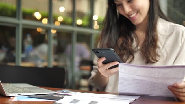 kvinna betalar bill på smart telefon - endast en ung kvinna bildbanksvideor och videomaterial från bakom kulisserna