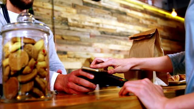 Woman paying bill through smartphone using NFC technology video
