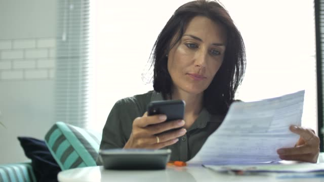 Woman paying bills with Mobile phone video
