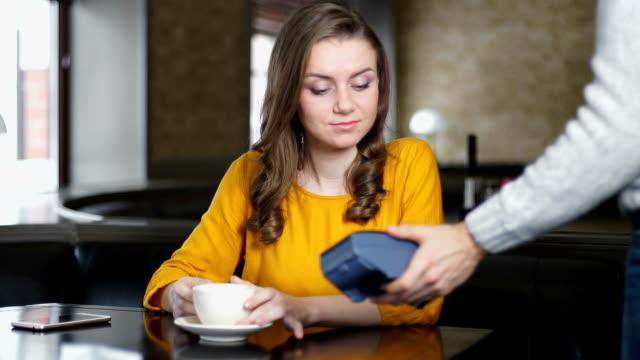 vídeos de stock e filmes b-roll de woman paying cafe bill with credit card through pin pad, contact less payment - paying with card contactless