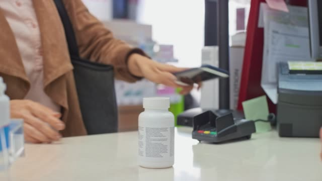 LD Woman paying for a bottle of vitamins at the drugstore using her smartphone Medium locked down shot of a woman paying for the supplements at the drugstore using her smartphone. Shot in Slovenia. nutritional supplement stock videos & royalty-free footage