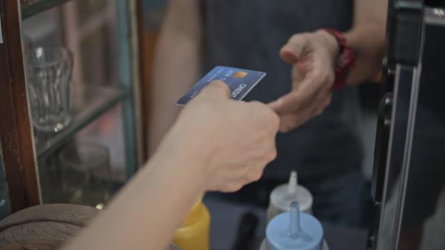 kvinna betalar för kaffe med kreditkort i ett café, slow motion - spendera pengar bildbanksvideor och videomaterial från bakom kulisserna
