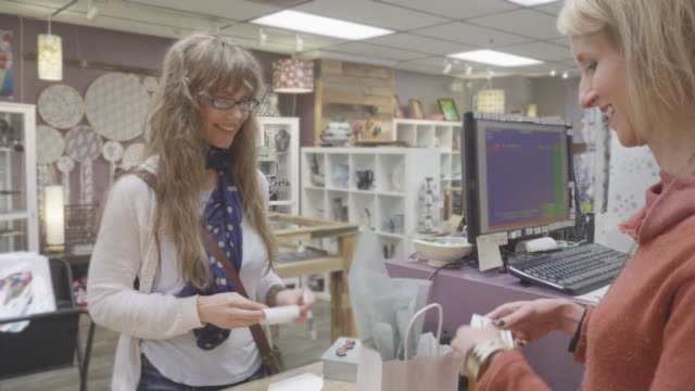 Woman Paying for Items at Cashier's Desk Attractive female shopper paying for items at cashier's desk. credit card purchase stock videos & royalty-free footage