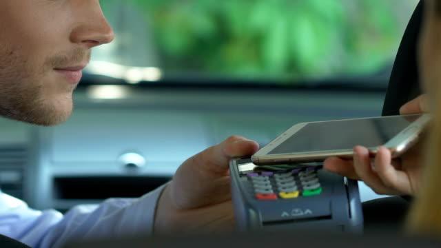 vídeos de stock, filmes e b-roll de mulher pagando de táxi através de aplicativo no smartphone, pagamento sem contacto - dividindo carro
