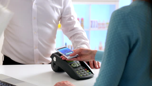 Woman paying through smartphone using NFC technology. Close up. Slow motion video