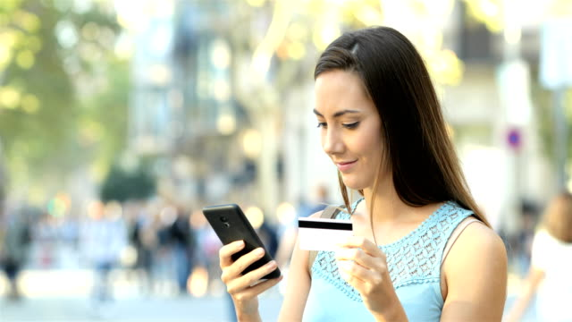 Woman paying with credit card and phone in the street Happy woman paying online with credit card and a smart phone in the street. E-commerce concept credit card purchase stock videos & royalty-free footage