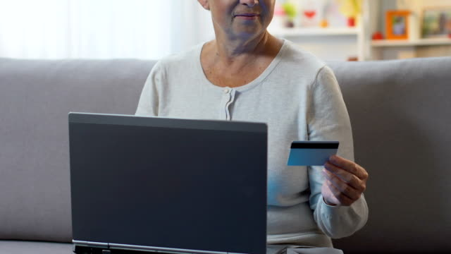 vídeos de stock e filmes b-roll de woman paying with credit card on laptop, easy banking service application - paying with card shop