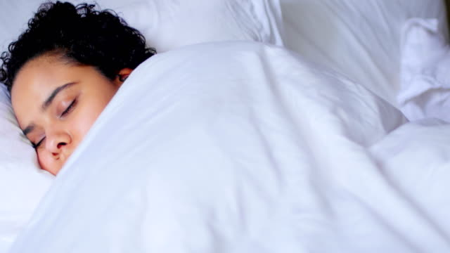 Woman peacefully sleeping on bed 4k video