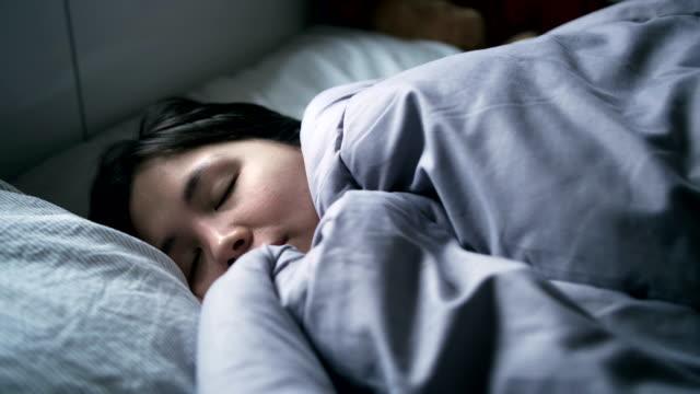 4k : woman peacefully sleeping on bed - kołdra filmów i materiałów b-roll
