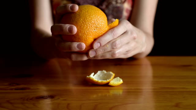 Woman peeling an orange video