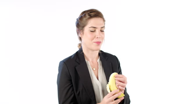 Woman peeling and eating a banana on a white studio background video