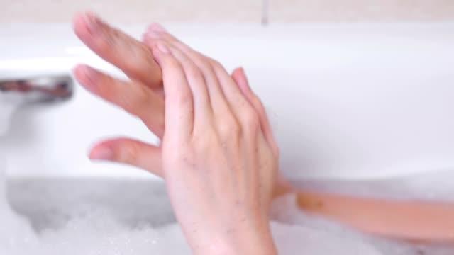 vidéos et rushes de femme se pelant les mains, met un gommage sur ses mains couché dans la salle de bain en mousse. les mains en gros plan. - cuticule