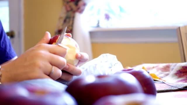 Mulher descascando a pele de uma maçã na cozinha durante os meses de outono - vídeo